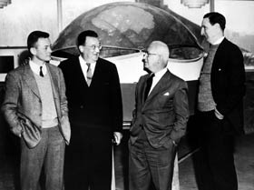Walter O'Malley visits Princeton University's School of Architecture where he meets with inventor R. Buckminster Fuller (second from right) regarding the design of a domed stadium for the Dodgers in Brooklyn. Fuller's graduate architecture students worked on the project at the request of O'Malley. The large scale model all-weather dome structure with a translucent roof was one possible design, while T. William Kleinsasser, Jr. (left) also tried to resolve the design problem as part of his master's thesis with a different domed model. Robert W. McLaughlin, Jr., director of the school, reviews the work on Nov. 22, 1955.