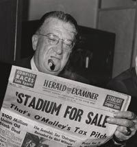 "Walter O'Malley reviews the headline from the Herald Examiner discussing the County Tax Assessor's desire to increase the assessed value of Dodger Stadium to $32.3 million on July 23, 1963. O'Malley was asked if he would be willing to sell the property for the new assessed value and he answered, ""You're darn right I would."""