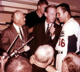 Vin Scully interviews relief pitcher Ron Perranoski in the jubilant Dodger clubhouse following the Dodgers' four-game sweep of the New York Yankees in the 1963 World Series. Dodger Vice President and Director, Minor League Operations Fresco Thompson is on far left.