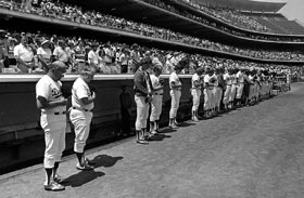 At Dodger Stadium, players and coaches bow their heads in memory of the man who brought the Dodgers to Southern California in 1958.
