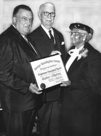 "Mrs. Mallie Robinson, the mother of Hall of Fame Dodger infielder Jackie Robinson, presents Walter O'Malley with the George Washington Carver Supreme Award of Merit for ""contributions to sports, better race relations and human welfare"" in 1959. University of Southern California President Rufus Von KleinSmid is in the middle."