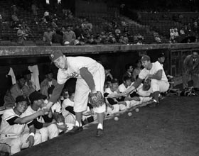 Shortstop Pee Wee Reese and first baseman Gil Hodges visit the opposing dugout and cultivate relationships before a game.