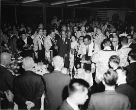 The Dodger players and officials wear hoppi coats at a reception welcoming their arrival in Japan. Walter O'Malley shakes hands with Mr. Matsutaro Shoriki, Publisher of the sponsor Yomiuri Shimbun.