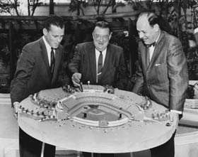 "Walter O'Malley inspects a model of Dodger Stadium with Vice President, Director of Stadium Operations Dick Walsh (left) and Executive Vice President and General Manager E.J. ""Buzzie"" Bavasi."