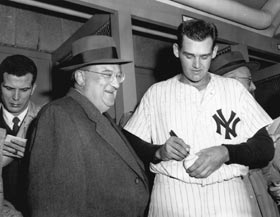 Gracious in defeat, Walter O'Malley receives an autograph from New York Yankees pitcher Don Larsen, who authored the only perfect game in World Series history — a 2-0 victory over Brooklyn in Game 5 in the 1956 Fall Classic.