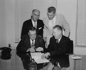 Walter O'Malley prepares to sign the official contract with the City of Los Angeles which will enable him to build Dodger Stadium, ending legal challenges on June 4, 1959. Seated next to O'Malley is Los Angeles City Council President John S. Gibson. Standing (l-r) is Councilman Ransom Callicott and City Attorney Roger Arnebergh.