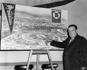 "At a news conference, O'Malley points out features of the proposed new Dodger Stadium, which will be built once L.A. voters pass the ""Proposition B"" measure on the June 3, 1958 ballot. O'Malley was ready to design, privately finance and build Dodger Stadium."