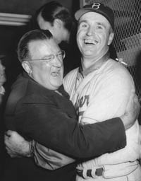 Jubilation in the Dodger clubhouse as Walter O'Malley and second-year Manager Walter Alston embrace as the Dodgers win their first World Championship on Oct. 4, 1955. The Dodgers defeated the New York Yankees, four games to three, with a 2-0 clincher in the seventh game at Yankee Stadium.