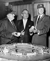 Walter O'Malley and Angels President Robert Reynolds trade hats in front of a model on Dec. 11, 1961. The Angels played at Dodger Stadium from 1962-65 before moving to Anaheim. In the center is Chad McClellan, who negotiated on behalf of the County and City of Los Angeles to bring the Dodgers to Los Angeles.