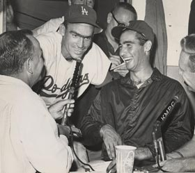 Sandy Koufax laughs as broadcasters Jerry Doggett and Vin Scully interview outfielder Wally Moon in the press box at the Los Angeles Coliseum.