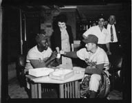 On their 1956 goodwill tour of Japan, the Dodgers were big hits with the appreciative fans. Jackie Robinson sits with star pitcher Carl Erskine and autographs baseballs for fans. Standing behind Erskine is Dodger clubhouse custodian Charlie DiGiovanna.