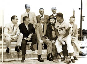 Walter O'Malley meets with Los Angeles elected officials during spring training at Dodgertown in Vero Beach, FL on March 6, 1957. County Supervisor Kenneth Hahn is on far left, while Los Angeles Mayor Norris Poulson is sitting third from left. Dodger center fielder Duke Snider sits on the lap of the famed clown Emmett Kelly, who was entertaining crowds during spring training.
