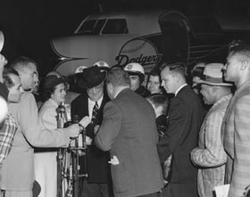 Walter O'Malley receives greetings from the press, politicians, and even a process server, upon landing in Los Angeles on Oct. 23, 1957.