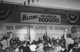 "The Dodgers are welcomed to Los Angeles at a huge party at the Statler Hotel on Oct. 28, 1957. Walter O'Malley is at the podium, while a banner behind him reads ""The Greatest Catch in Baseball."""