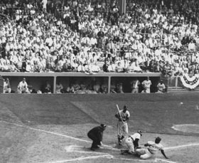 Jackie Robinson steals home during the World Series against the New York Yankees.