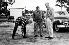 Bud Holman (left) bends down and checks the soil as Walter O'Malley and noted designer Capt. Emil Praeger review a possible site for a new stadium at Dodgertown.