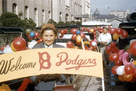 "Kay O'Malley rides along the ""Welcome Dodgers"" motorcade in Japan."