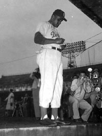 Pitcher Don Newcombe signs autographs prior to a game.