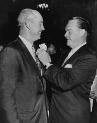 "Los Angeles Examiner columnist Vincent X. Flaherty pins a flower on Dodger Manager Walter Alston at a ""Welcome Dodgers"" luncheon prior to the 1958 season opener. Flaherty initially corresponded with Walter O'Malley in 1953, expressing the interest of Los Angeles officials to bring Major League Baseball to the West Coast."