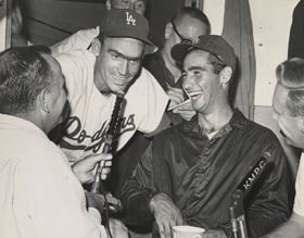 Jerry Doggett interviews outfielder Wally Moon on KMPC Radio in the press box of the Los Angeles Memorial Coliseum as pitcher Sandy Koufax and broadcaster Vin Scully look on.