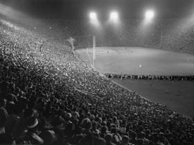 "A major league-record crowd of 93,103 attends ""Roy Campanella Night"" at the Los Angeles Memorial Coliseum for a special exhibition game between the Dodgers and the New York Yankees on May 7, 1959. The teams played in honor of Campanella, the three-time National League MVP, who was paralyzed from the neck down in an automobile accident on Jan. 28, 1958. Fans attending may forget the Yankees won, 6-2, but they will always remember each person being asked to light a match in unison to pay tribute to ""Campy."""