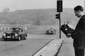 In addition to baseball, Dodger Stadium was used for other sporting events. This road race on March 2 and 3, 1963 took advantage of the spacious parking lot around the ballpark. Robert E. Egan, Senior Investigator for the City's Department of Building and Safety checks the noise level of sports cars in the parking lot as the Dodgers seek a permit for the races. Photo taken Nov. 21, 1962.