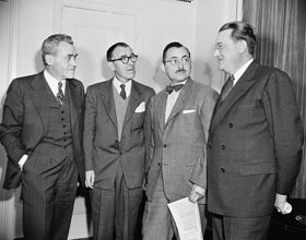 Walter O'Malley, part-owner of the Dodgers (on far right), speaks with Dodger part-owner John L. Smith (far left), Eddie Brannick of the New York Giants (second from left) and Jimmy Gallagher of the Chicago Cubs during a meeting of the National League in New York on January 31, 1947.