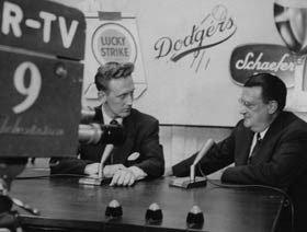 Walter O'Malley appears on television with Dodger broadcaster Vin Scully.