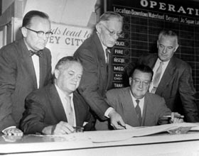Walter O'Malley confers with Jersey City, NJ officials to use Roosevelt Stadium for selected Dodger home games in 1956 and 1957 on Aug. 22, 1955, while he tries to find a permanent solution to the aging Ebbets Field problem. Seated next to O'Malley is Mayor Bernard Berry of Jersey City, while standing from left are Jersey City Comissioners Lawrence Whipple and Joshua Ringle, along with Dodger Vice President Fresco Thompson.
