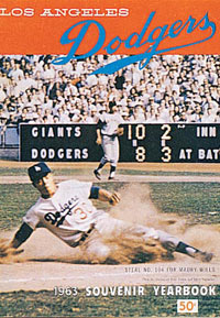 The 1963 Dodger Yearbook features shortstop Maury Wills sliding into third base en route to a record-breaking season for stolen bases (104) in 1962. Wills suffered a leg injury in the first game of 1963, but still managed to steal 40 bases to once again lead the National League for the fourth straight season.