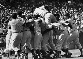 The Dodgers go wild in celebrating the 1963 World Championship at Dodger Stadium. First baseman Ron Fairly (No. 6) leaps atop the pack, as Game 4 complete-game pitcher Sandy Koufax is mobbed by his teammates following a 2-1 victory. Koufax was named World Series MVP, winning two games, while pitchers Johnny Podres and Don Drysdale each won one game.