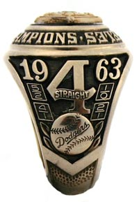 "Walter O'Malley's 1963 World Championship Dodger ring, which he designed along with Balfour representative Bill Stuckman, features 14-karat white gold and the wording '4 Straight' plus the scores of the World Series games on one shank. On the top, or bezel, it reads ""Los Angeles World Champions"" with a blue sapphire. The other shank showed the player's name and crossed bats."