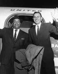 Roy Campanella and teammate Gil Hodges wave to well-wishers after stepping off a Dodger charter flight.