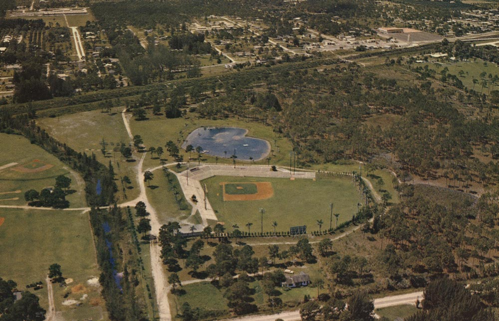"A color aerial view of Historic Dodgertown showing Holman Stadium and the heart-shaped lake by the ballpark.  The lake in its shape was a tribute from Walter O'Malley to his wife, Kay. In 1962, despite the presence of Southern ""Jim Crow"" laws, Walter and Peter O'Malley made seating integrated allowing any baseball fan to sit wherever they pleased at Dodgertown."