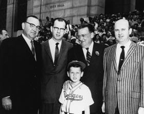 "On the steps of City Hall in Los Angeles before the first game in Los Angeles on April 18, 1958, are (l-r) California Attorney General Edmund G. ""Pat"" Brown, Los Angeles County Supervisor Kenneth Hahn, Walter O'Malley, Los Angeles City Councilman Gordon Hahn and Kenneth's son and honorary batboy, James. ""Pat"" Brown became Governor of California in 1959, while James Hahn served as Mayor of Los Angeles from 2001-05."