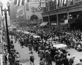 Thousands of fans line the streets of downtown Los Angeles to greet a parade of Dodger players and coaches. The parade is in honor of Opening Day, April 18, 1958 and the first Major League game to be played in Los Angeles. The parade route made its way through downtown to the Los Angeles Memorial Coliseum.