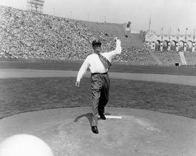 "Los Angeles Mayor Norris Poulson, an influential civic leader in bringing the Dodgers west, is shown throwing the ceremonial first pitch on the mound of the Los Angeles Memorial Coliseum on April 18, 1958. Poulson is wearing a baseball tie that reads, ""Los Angeles Dodgers."""