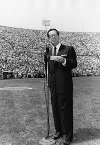 Comedian and first game in Los Angeles emcee Joe E. Brown speaks during ceremonies at the Los Angeles Memorial Coliseum on April 18, 1958.
