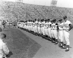 Los Angeles Dodgers and San Francisco Giants take their positions for pregame introductions for the opening game in Los Angeles on April 18, 1958 at the Los Angeles Memorial Coliseum.