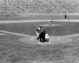 The first pitch of Major League Baseball in Los Angeles is thrown by right-hander Carl Erskine to Giant third baseman Jimmy Davenport on April 18, 1958 at the Los Angeles Memorial Coliseum.