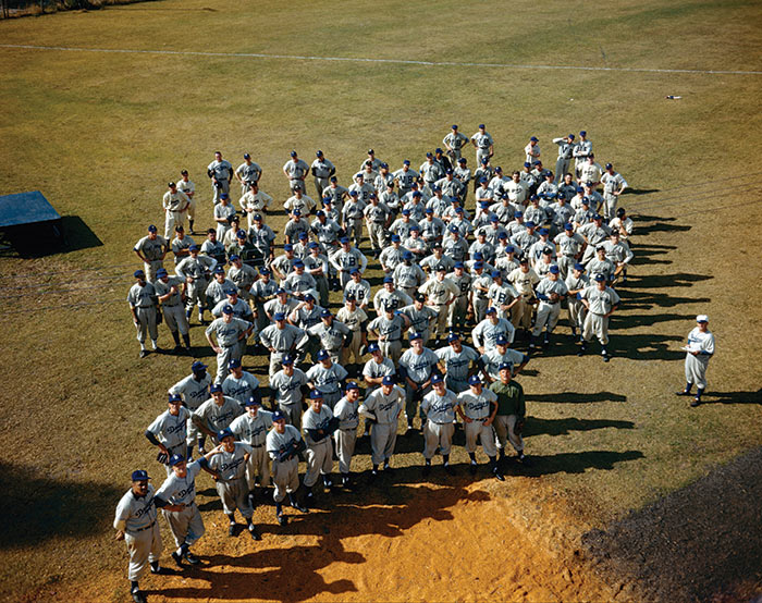 An aerial color view of Dodger players at Dodgertown in Vero Beach in the late 1940s, reminiscent of the LIFE magazine cover of minor league Dodger players in 1948.  Don Newcombe, the only major league player ever to win the Rookie of the Year, the Most Valuable Player Award and the Cy Young Award, stands on the far left in the first row at the front.  Jackie Robinson, the first African-American to play in the major leagues in the modern era, stands on the far left in the third row.  Fresco Thompson, the Dodgers' minor league director, stands on the far right wearing a white Brooklyn hat.