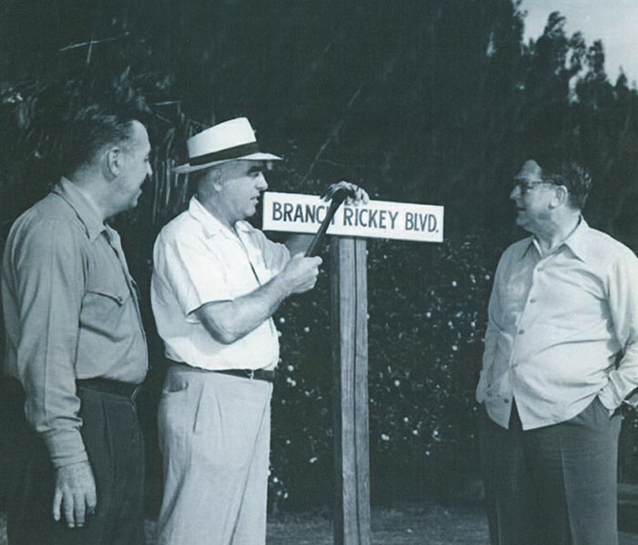 """(L-R) Dodgertown Director Spencer Harris; Vero Beach business leader Bud Holman; Branch Rickey. A Dodgertown tradition is to name a street after a Dodger player or person has been named to the Hall of Fame. Here, Bud Holman, prominent Vero Beach business leader for whom Holman Stadium was later named, adds the final touches to a street sign """"Branch Rickey Boulevard"""" for the current Dodger President in 1948, the first season for Dodgertown. Rickey was later elected to the Baseball Hall of Fame in 1967."""