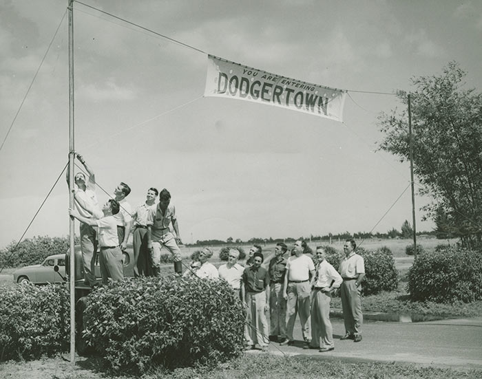 1948 Dodgertown employees raise a welcoming banner to everyone who is staying on the Dodgertown base in Vero Beach, Florida for Spring Training. The banner concept remained a Dodgertown tradition for players for the next 60 seasons. In 1948, it marked the first integrated Spring Training Camp for baseball in the South where all players, regardless of color, shared the same dining and living accommodations.