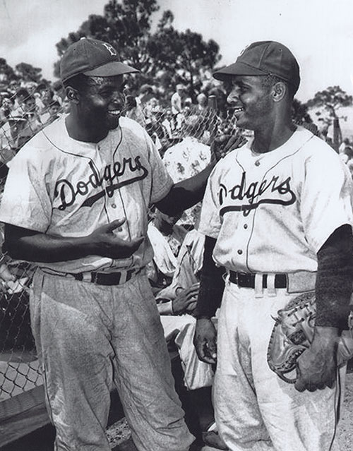 (L-R) Jackie Robinson; Roy Campanella. Jackie Robinson offers a congratulatory handshake to catcher Roy Campanella, March 31, 1948. The Brooklyn Dodgers have acquired Campanella from their Montreal AAA minor league team to add him to the Dodgers' major league roster. On this date, the game is the first to be played by the Brooklyn Dodgers in Vero Beach at Dodgertown, the first racially integrated Spring Training camp in the South.