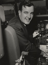 """Capt. Harry R. """"Bump"""" Holman is seated in his familiar cockpit chair ready for another flight with the Dodgers. Today, Holman and his brother Tom own Sun Aviation at Vero Beach, Florida. They now have 50 employees in their avionics and maintenance departments."""