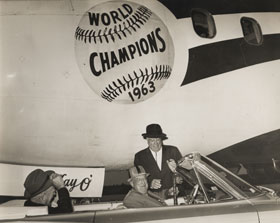 """Bud Holman (standing), Bump's father, greets Dodger President Walter O'Malley who arrives in a car on the tarmac, with the """"Kay O'"""" Dodger Electra II seen in the background."""