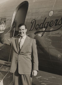 In front of the Dodger DC-3 airplane, Bump Holman prepares for a flight with the Dodger organization. Most of the time, Holman flew the Vero Beach, Florida-based plane around the state of Florida, taking the Dodgers to Spring Training games. But, in 1954, Dodger executives decided to experiment for a season by flying the minor league St. Paul, MN club on its road trips in the DC-3 with Holman at the controls. This continued for two more seasons, expanding to the Ft. Worth, TX minor league club before the major league Dodgers were flown in the new Convair 440 Metropolitan in 1957.