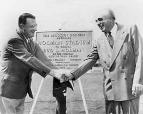 """Walter O'Malley and Bud Holman shake hands at the dedication ceremonies for Holman Stadium on March 11, 1953. Though he became a rabid Dodger fan, initially Holman knew little about baseball. As an astute businessman, he saw and acted on the opportunity to bring the Dodgers to Vero Beach for spring training. The plaque presented by the Dodgers reads, """"The Brooklyn Dodgers Dedicate Holman Stadium to Honor Bud L. Holman of the Friendly City of Vero Beach, Walter F. O'Malley, President, Emil H. Praeger, C.E., Designer, 1953."""""""