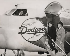 Dodger President Walter O'Malley and Dodger Director Bud Holman are on the steps of the 44-seat Dodger Convair 440 Metropolitan twin-engine plane. Holman's son Bump is visible in the cockpit window. O'Malley added to the order of Eastern Air Lines to purchase the plane directly through the Convair factory, with the assistance of his friend Capt. Eddie Rickenbacker, President of Eastern. Bud Holman served as a Director of the Dodgers and was Eastern's representative at the Vero Beach Airport.