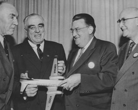 The Dodgers became the first major league baseball team to own their own airplane, as they purchased a Convair 440 Metropolitan twin-engine. From left to right, Capt. Eddie Rickenbacker, President of Eastern Air Lines, Dodger Director Bud Holman, Dodger President Walter O'Malley and Dodger Director James Mulvey show a model of the Convair 440. The Dodgers made the purchase of the airplane on January 4, 1957, piggybacking on Rickenbacker's order of airplanes for Eastern.